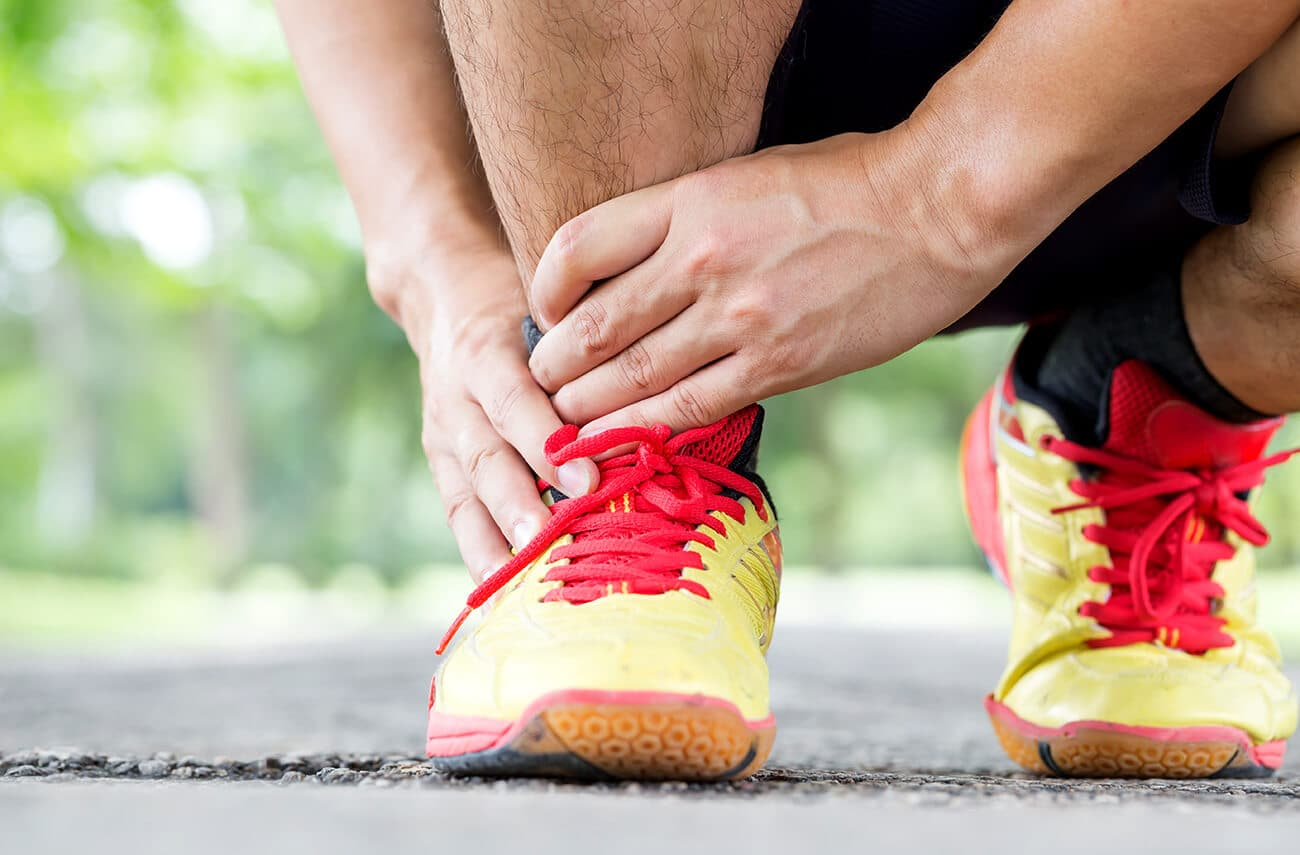 picture of a man running but holding his foot and ankle after suffering an ankle sprain